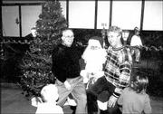 Bob McGreevy, Knights of Columbus homes president, left, and Mark Klug, club treasurer, sit on Santa's lap. Grand Knight John Callewaert was Santa at the club's annual children's Christmas party on Dec. 6 at the Knights of Columbus, 2206 E. 23rd St.