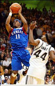 Kansas University's Aaron Miles (11) breezes past Colorado's Lamar Harris. The Jayhawks beat the Buffaloes, 77-62, Monday night in Boulder, Colo.