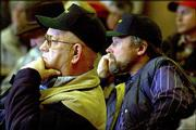 Walter Coker, left, of Topeka, and Rich Runnenbaum, a farmer from Berryton, listen to the panel discussion about mad cow disease given by the Kansas Livestock Assn. The two were attending a farm show Tuesday in Topeka.