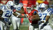 Kansas City running back Priest Holmes, center, fights off Indianapolis defenders David Macklin, right, and Walt Harris. Holmes fumbled on the play, and Macklin recovered for the Colts. The play proved costly for the Chiefs in a 38-31 loss Sunday in Kansas City, Mo.