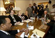 Michael Jackson's music manager, Charles Koppelman, seated at the head of the table at right, with defense lawyer Mark Geragos, standing at left, and Nation of Islam chief of staff Leonard Muhammad, seated far left, along with Jackson's closest advisers have an all-day meeting Monday at the Beverly Hills Hotel in Beverly Hills, Calif., to discuss the singer's legal and financial strategy. Jackson is scheduled to be arraigned Friday in Santa Maria, Calif., on child molestation charges.