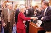Kansas Gov. Kathleen Sebelius greets Rep. Stan Dreher, an Iola Republican, while leaving the House chamber after her State of the State address. At left is Rep. Melvin Neufeld, an Ingalls Republican, who attended Monday's speech.