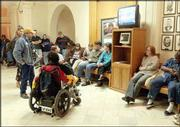 A small group of advocates for people with disabilities watches the televised State of the State address at the Capitol in Topeka. Gov. Kathleen Sebelius' proposals for social service programs did not go far enough to satisfy many who work in the field.