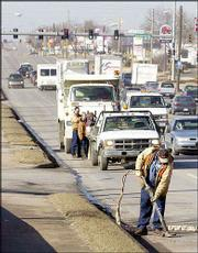 Willie Harris, Lawrence, seals cracks in the curbs and road on 23rd Street. The city plans to enforce new rules to require traffic-impact studies for proposed development as well as impose a new access-management system for the entire city. Harris, a city street department employee, worked Monday.