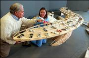 Richard Gwin/Journal-World Photo Dennis Sander, a Kansas University associate professor of architecture and urban design, shows his daughter, Erika, a model for a museum dedicated to the 24 hours of Le Mans auto race. Sander will pitch the project, built with the help of a class of third-year architecture students, to race officials this year.