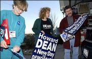 Howard Dean supporters, from left, Marjorie Swindler, Lauren Sullivan and Rex Powell, examine campaign advertising at Sullivan's Lawrence house. Sullivan is heading to Iowa for the first caucuses of 2004. Swindler and Powell just returned from Des Moines, Iowa, where they were campaigning.
