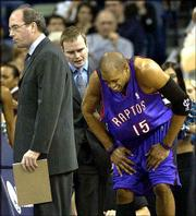 Toronto's Vince Carter (15) grimaces while getting to his feet. Carter, who injured his right leg, was helped by trainer Chuck Mooney, middle, while coach Kevin O'Neal headed back to the bench Thursday at New Orleans. The Raptors beat the Hornets, 78-74