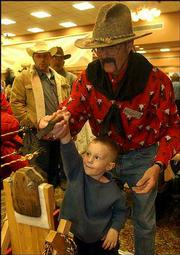 Bob Ivins shows Dalton Lesher, 4, of Lawrence, how to make rope Saturday at the gathering. Ivins travels to similar shows year-round.