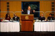 Kansas University football coach Mark Mangino addresses a crowd at a banquet in honor of the Martin Luther King Jr. holiday. Seated, from left, are Izetta Taylor, the Rev. Verdell Taylor, the Rev. Leo Barbee Jr. and Climetine Clayburn, Kennedy School principal.
