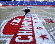 Stadium worker Joe Diorio paints a logo on the field at Gillette Stadium in preparation for today's AFC championship game between the Indianapolis Colts and the New England Patriots. Diorio worked Saturday in Foxboro, Mass.