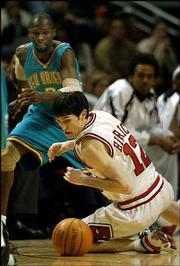 Chicago's Kirk Hinrich (12) dives for a ball in front of New Orleans' Darrell Armstrong during a game Jan. 10. Bulls fans -- and coach Scott Skiles -- admire Hinrich's work ethic and hustle.
