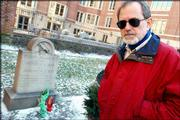 Jeff Jerome, curator at the Poe House and Museum in Baltimore, stands near author Edgar Allan Poe's grave in Baltimore. This year's traditional offering of roses and cognac on the anniversary of Poe's birth was accompanied by a note taking a jab at the French.