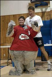 Matt Breshears, a sixth-grader at Veritas Christian School, gets helped into the KC Wolf mascot costume by Dan Meers, who has performed as the Kansas City Chiefs mascot for 14 years. Breshears was honored in a school assembly Tuesday for being one of 23 winners in a poster-drawing contest.