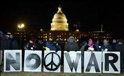 Anti-war demonstrators hold signs outside the Capitol during President Bush's State of The Union address. Tuesday, Bush defended the nation's ouster of Saddam Hussein.
