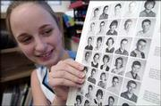Holly Maygers, a ninth-grader at West Junior High School, displays a page of student school portraits from an early-1960s yearbook. The West yearbook staff is selling surplus Warhawk yearbooks dating from 1961 to 2003 to raise money.