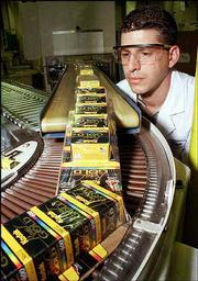 Kodak technician Dan Merola inspects boxes of Kodak Royal Gold film coming off a packaging line in Rochester, N.Y. Eastman Kodak Co., struggling to find its footing in new digital photography markets as its signature film business fades, said Thursday it would cut from 12,000 to 15,000 jobs, or up to 23 percent of its global work force, during the next three years.