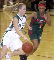 Free State's Emily HUmbarger, left, pushes past Topeka Highland Park's Cherice Swopes during second-half play. The Scots downed the Firebirds, 56-63, Friday night at Free State.