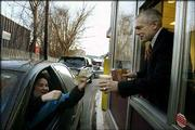 Democratic presidential candidate Wesley Clark, right, works the drive-through window at a Dunkin' Donuts during a campaign stop in Derry, N.H. The Democratic candidates were working Friday to capture the support of still-undecided voters before New Hampshire's first-in-the-nation primary Tuesday.