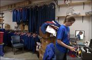 Kansas University Band member Abby Huckvale, Winfield senior, browses through a row of the more than 500 band uniforms in Murphy Hall, many of which are ragged and beyond repair. The marching band is hoping to replace them with new uniforms. The price tag: $150,000 for 300 uniforms.