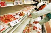 An employee removes packs of chickens imported from Thailand from shelves at a supermarket in Nagoya, central Japan. Japan has banned Thai chicken imports because of the proliferation of bird flu in Thailand.