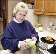 Kenna Frankenfeld prepares a meal of chicken casserole and lettuce. Frankenfeld, who has lost more than 100 pounds on the Atkins diet, prepared her meal Monday in her Lawrence home.