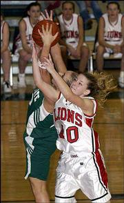 Lawrence High's Jodie Cochrane, foreground, fights for a rebound with Free State's Jamie Stanclift. LHS beat FSHS, 48-29, Saturday in the fifth-place game of the Firebird Winter Classic.