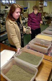 Lorraine Palmer, left, and Johnita Crawford, co-owners of the Cloud County Tea Co. in Clyde, prepare some of the imported herbs used in blending their gourmet teas. Their business is housed in a former Baptist church, where blending and packaging is done in the basement, the showroom is on the main floor and a library is in the choir loft.