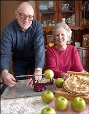 Lyle Brubaker demonstrates a machine that cores and peels apples while his wife, Lois, displays her homemade apple pie. Lois plans to donate two homemade pies to Saturday's Pie Sale and Quilt Show at Plymouth Congregational Church. The event raises money for Interfaith Caring Neighbors, an agency that provides help for the elderly.