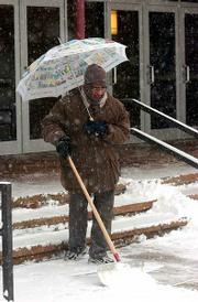 Subramania Natrajan, a Kansas University employee who works at Murphy Hall, used an umbrella Thursday morning to ward off heavy snow as he shoveled the sidewalk.