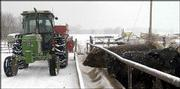 Doug Geist, who works at Nunemaker-Ross Inc., delivers feed to the farm's cattle. Geist was working Thursday at the farm in North Lawrence. Area farmers said they welcomed the snow despite the extra work that came with it.