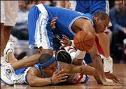 Los Angeles' Devean George, top, and Derek Fisher, bottom sandwich Philadelphia's Allen Iverson while chasing a loose ball. The 76ers defeated the Lakers, 96-73, Thursday night in Philadelphia.