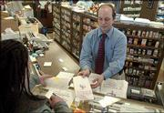 Tim Bredehoft, pharmacist at Medical Arts Pharmacy, 346 Maine, gives a customer her medication. A Journal-World survey of Lawrence pharmacies on Thursday revealed that prices of some popular drugs can vary greatly, depending on where you shop.