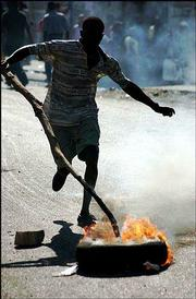 A student runs with a burning tire during a protest against Haiti's President Jean- Bertrand Aristide in Port-au-Prince, Haiti. Opposition groups protested Wednesday in the nation's capital and freed prisoners and lit fires Thursday in Gonaives.