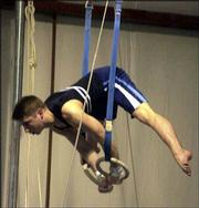 Scott Bregman performs a stunt on the rings during a Lawrence Gymnastics Academy meet. Bregman, who has attained Class1 Junior Elite status, is hoping he can use his athletic ability to earn a college scholarship, but opportunities are limited.