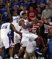 Kansas University's Wayne Simien tears away from Texas Tech's Michael Marshall, right, for one of Simien's game-high 17 rebounds as KU's Michael Lee, left, and Keith Langford (5) defend. Simien also had a team-high 22 points in the Jayhawks' 96-77 rout of the Red Raiders Saturday at Allen Fieldhouse.