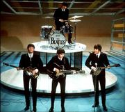 "The Beatles perform on CBS&squot; ""The Ed Sullivan Show"" Feb. 9, 1964, in New York. From left, front, are Paul McCartney, George Harrison and John Lennon. Ringo Starr plays drums."