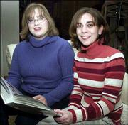 Tiffany Muller, right, and Erin Norris hold their wedding album at home in Topeka. The idea that Muller and Norris, or other same-sex couples could marry legally someday has legislators considering a proposed constitutional amendment to reinforce Kansas' long-standing policy against recognizing such unions.