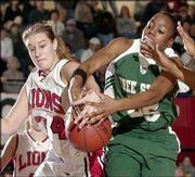 Lawrence High's Megan Klinger, left, battles for possession with Free State High's Banaka Okwuone. The Lions knocked off the Firebirds, 63-51, Saturday at LHS.