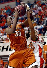 Texas forward Tiffany Jackson, left, grabs a rebound over Oklahoma State guard Nina Stone. The Longhorns won, 75-52, Saturday in Stillwater, Okla.