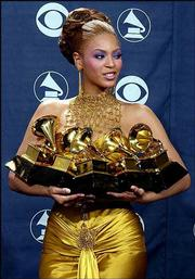 Beyonce Knowles holds her record-tying five awards during the 46th annual Grammy Awards.