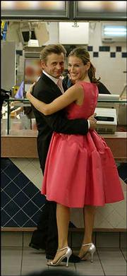 "Carrie (Sarah Jessica Parker) and Aleksandr (Mikhail Baryshnikov) are shown in an episode from the sixth season of ""Sex and the City"" in which Aleksandr surprises Carrie with an Oscar de la Renta dress."