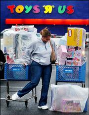 "Carolyn Hardy struggles to maintain two shopping carts filled with toys at Toys ""R"" Us in Birmingham, Ala., in this Nov. 28 photo. After the brutal price wars that claimed two toy store chain casualties this past holiday season, toymakers say they&squot;re standing up to some of the discount retailers, particularly Wal-Mart Stores Inc., to protect themselves and the industry."