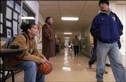 Haskell Indian Nations University students Honey Round Face, left, chats with her brother, Theodore Round Face, as he passes by on his way to class. Standing second from left, is Kemo Sauba, from Grand Rapids, Mich. The Round Faces, from Pryor, Mont., spoke Friday in the hallway of Haskell''s Sequoyah Hall. Honey carried a ball with her for good luck before Friday's women's basketball game.