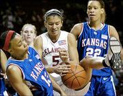 Oklahoma's Maria Villarroel (5) tries to gain control of the ball as Kansas University's Larisha Graves and Tamara Ransburg (22) defend. The Sooners beat the Jayhawks, 83-59, Saturday in Norman, Okla.