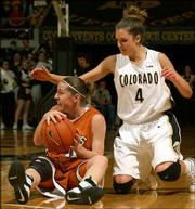 Texas guard Jamie Carey, left, looks for help after scooping up a loose ball as Colorado guard Emily Waner (4) closes in. The top-ranked Longhorns held off the No. 12 Buffaloes, 51-45, Saturday in Boulder, Colo.