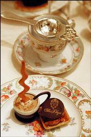 A table setting for tea time at The Plaza Hotel's Palm Court reflects its historical elegance and tradition.