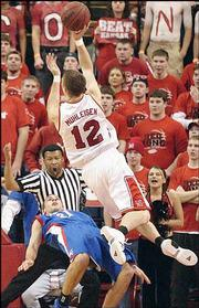 Kansas University walk-on Nick Bahe tries -- unsuccessfully, as can be told by the official's call -- to draw a charge against Nebraska's Jake Muhleisen (12) late in the Cornhuskers' 74-55 victory. NU's win over KU Sunday in Lincoln, Neb., was Nebraska's first over Kansas in 10 meetings.
