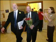 Rich Walker, left, and Brad Chilcoat are applauded after receiving their marriage license at City Hall in San Francisco. In a political challenge to California law, city authorities continue to issue more same-sex marriage licenses; however, so many were requested Sunday that officials had to turn away couples.