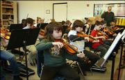 Fourth-graders learn to play the violin at Chase County Elementary School in Cottonwood Falls. Instruments are donated to the school so that interested students can learn to play. Chase County Elementary is an example of one school that steps in to provide many services to students and their families beyond curriculum. The school serves meals, enrolls children in after-school clubs, operates a clothing bank and serves as roller-skating rink, among other things.