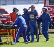 Michael Waltrip is escorted by safety workers to an ambulance after an accident. He didn't finish the Daytona 500 Sunday at the Daytona International Speedway in Daytona Beach, Fla.